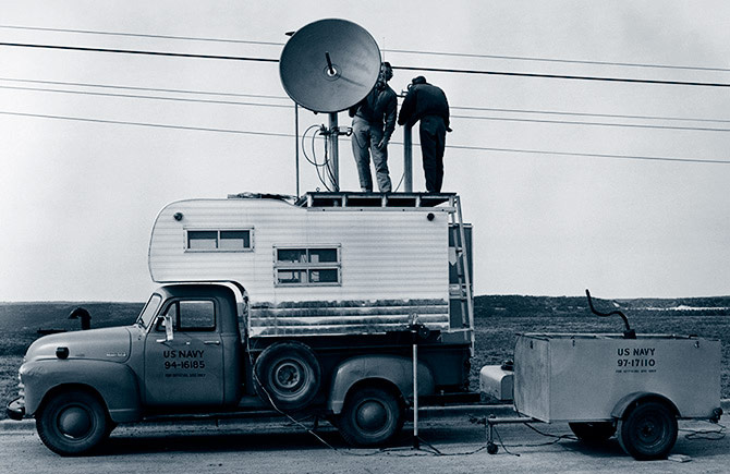 Two men with transmitters on top of a truck with a camper in the bed using radio transmitters in the late 1940s-1950s